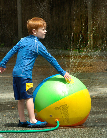 BRYAN EATON/ Staff Photo. Hayden Luck, 5, plays with a beach ball turned into a sprinkler at the Brown School playground yesterday. It was Water Day for the children to celebrate the end of the school year.