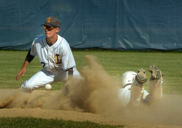 BRYAN EATON/ Staff Photo. Pentucket's DJ Englke is in the dust as throw is late to the Lynnfield shortstop giving him the steal to second.