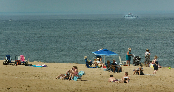 BRYAN EATON/ Staff Photo. People lay in the 90-plus degree temperatures at Plum Island Center on Wednesday as a party boat is seen in the distance