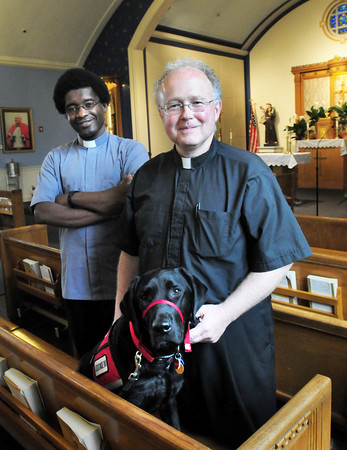 BRYAN EATON/Staff Photo. Fr. Scott Euvrard, right, pastor of the collaborative of Holy Family Parish in Amesbury and Star of the Sea Parish in Salisbury, with Lazer, and Fr. Ixon Chateau, vicar of the collaborative parishes.