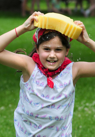 BRYAN EATON/ Staff Photo. Olive McLin, 7, runs with a wet sponge on her head in a relay with other teams to fill a bucket with the cerebral-supported water, the first to do so winning the contest. She was at the Inn Street Montessori's annual Field Days on Monday afternoon.