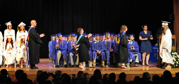 BRYAN EATON/ Staff Photo. Georgetown High graduates receive their diplomas Saturday from Barbie Linares, chairman of the school committee.