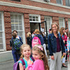 BRYAN EATON/ Staff Photo. Kindergarten friends Zinnia Hopkinson, left, and Lucy Rimer, both 6, embrace as they leave the Brown School yesterday. They head to the new Bresnahan in fall and hope they're in the same class again.
