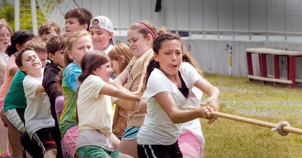 BRYAN EATON/ Staff Photo. The winning team in the final heat of a game of tug-of-war struggle as they carry their opponents over the line Tuesday morning. The Amesbury Middle School students were having their Field Day at Landry Stadium.