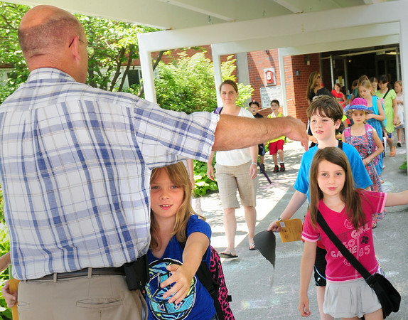 BRYAN EATON/ Staff Photo. Amesbury Elementary School principal Walter Helliesen gets hugs from some of his students as Amesbury Schools let out yesterday morning for summer vacation.