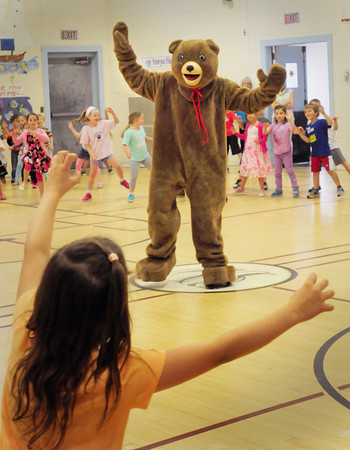 BRYAN EATON/ Staff Photo. The Brown School Bear leads the youngsters to an up tempo version of the Itsy Bitsy Spider during yesterday's farewell assembly.