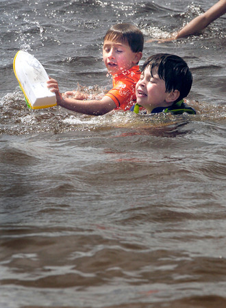 BRYAN EATON/ Staff Photo. Maxx Rodrigues, 6, left, and friend Christian Sullivan, 5, of Amesbury play in the choppy water caused by the strong wind at Lake Gardner Beach yesterday afternoon. Though the temperature approached 90 degrees, the wind made it seem cooler.