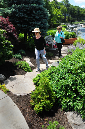 BRYAN EATON/ Staff Photo. Chris Martin, left, and Linda Connell both of Amesbury check out the gardens at Greg Southare's home this weekend at the Point Shore Gardent Tour. Money raised is to help preserve the Union Congregational Church across from Alliance Park.