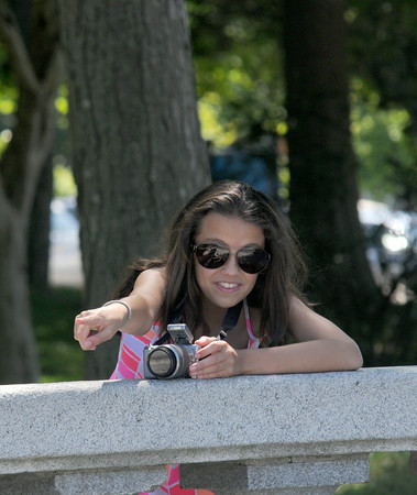 JIM VAIKNORAS/Staff photo  Yanna Haginicolas, 12, gives some direction to her subjects as she takes photo on a warm summer day in Market Landing park in Newburyport Friday.