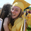 JIM VAIKNORAS/Staff photo Bryn Willingham hugs fellow Newburyport high graduate Emma Hill after graduation Sunday at War Memorial Stadium. The pair are taking a gap year to travel to Bali.