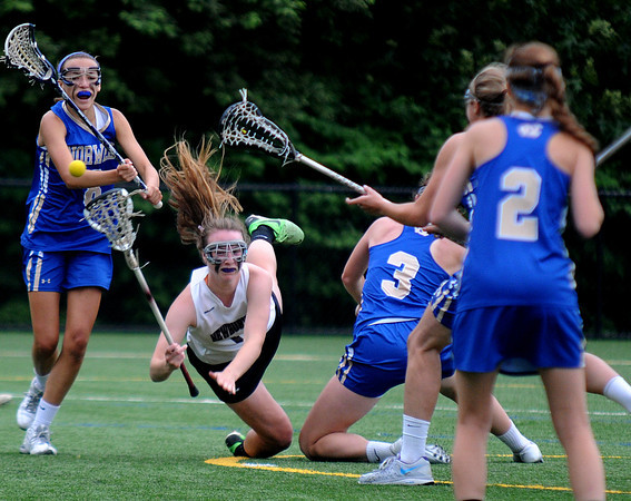 JIM VAIKNORAS/Staff photo Newburyport's Lilly Donavan passes the ball as she falls against Norwell at Babson College in Wellesley Monday night. The Clippers won the game and will play for the state title Saturday at BU.
