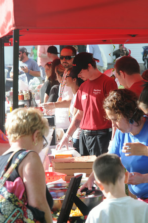 JIM VAIKNORAS/Staff photo  People try samples from local vendors at the Amesbury Day's Block Party Thursday night.