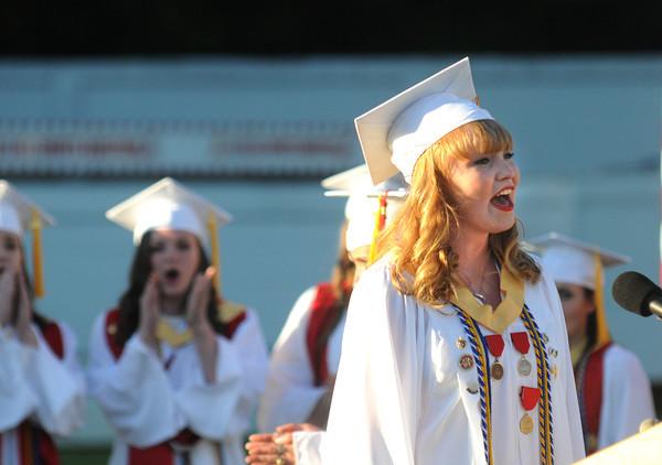 JIM VAIKNORAS/Staff photo Amesbury's Kayla Murphy sings the National Anthem at the start of Amesbury graduation at Landry Stadium.