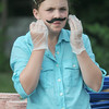 JIM VAIKNORAS/Staff photo Brigid Woelfel , 11, fixes her mustache before serving burgers at the Amesbury Day's Block Party Thursday night.