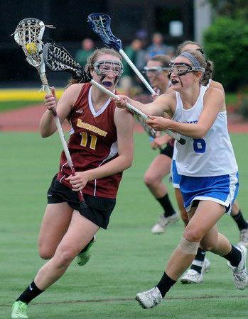 JIM VAIKNORAS/Staff photo Newburyport 's Lilly Donovan makes a move around Bromfield's Greer Jarvis during Staurday's state championship game at Boston University. The Clippers won the game and the chamionship 7-6.