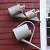 JIM VAIKNORAS/Staff photo  Watering cans in the garden of Joe and Carol Flynn at 412 Main Street in Amesbury.