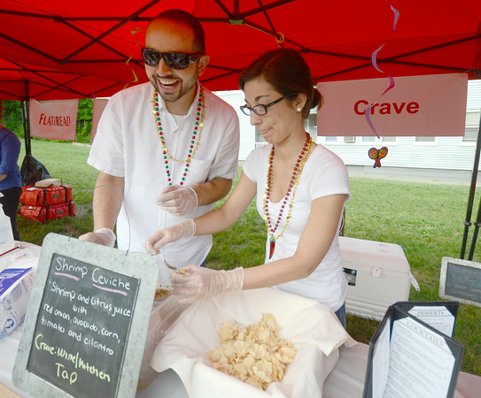 JIM VAIKNORAS/Staff photo Sean Toomey and May Prando of Crave in Amesbury serve ceviche  at the Amesbury Days Block Party Thursday night.