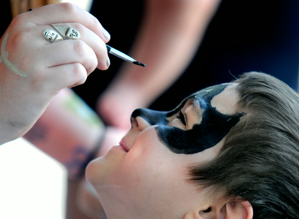 JIM VAIKNORAS/Staff photo Liam Soucy , 4, gets a Batman mark painted on his face by Hannah Knittle at the Amesbury Days Farmer Market at City Hall Saturday.