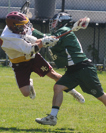 JIM VAIKNORAS/Staff photo Newburyport's Tanner Derby shoots as he is being checked by Austin Prep's Michael Russell during their game at War Memorial Stadium in Newburyport Saturday.