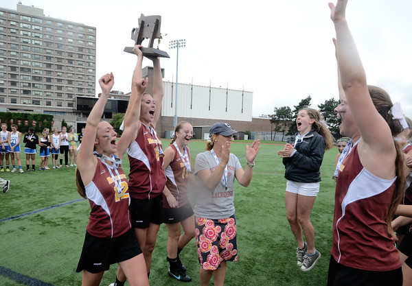 JIM VAIKNORAS/Staff photo Newburyport girls lacrosse Coach Catherine Batchelder and her captains Alex Peffer, Julia Kipp and Kelly Conway carry the state championship trophy back to their team. The Clipper dfeated Bromfield 7-6 to win the title at BU Saturday.