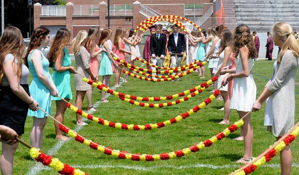 JIM VAIKNORAS/Staff photo Newburyport high graduates enter War Memorial Stadium under the Arch of Roses Sunday.
