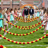 JIM VAIKNORAS/Staff photo Newburyport high graduates enter War Memorial Stadium under the Arch of Roses Sunday.