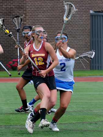 JIM VAIKNORAS/Staff photo Newburyport 's Alexandra Peffer makes a move around Bromfield's Marcy Shappy during Saturday's state championship game at Boston University. The Clippers won the game and the chamionship 7-6.
