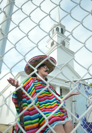 JIM VAIKNORAS/Staff photo<br />  Amesbury City Councilor Anne Ferguson, dressed in poncho and sombrero, wait to be dunked in the dunk tank at the Amesbury Days Block Party thursday night.