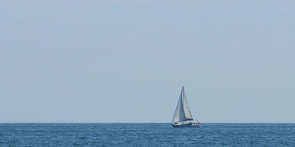 JIM VAIKNORAS/Staff photo <br /> A sail boats glides along a clean horizon off Salisbury Beach Saturday afternoon.