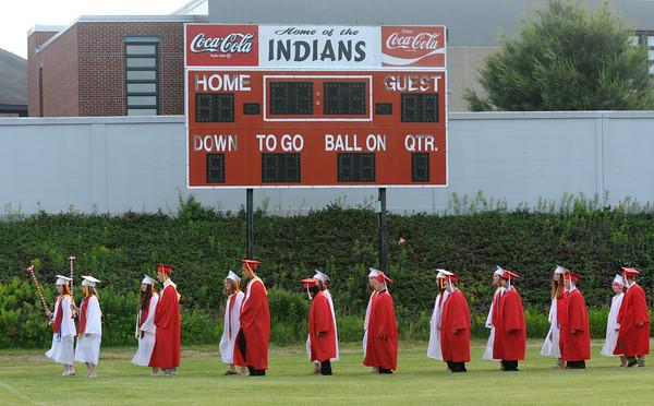 JIM VAIKNORAS/Staff photo <br /> Amesbury graduates march in under the scoreboard at Landry Stadium Friday night.