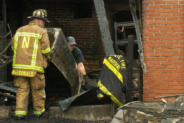BRYAN EATON/Staff photo. Firefighters remove items from the back of the patio at Abraham's.