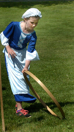 """BRYAN EATON/Staff Photo. Olivia Foley, 8, rolls a barrel hoop along Newbury's Upper Green playing Colonial games with other third-graders from the Bresnahan School in Newburyport. A new program titled """"Colonial Day"""" facilitated by Historic New England brought the students to several of their properties to learn to make butter and other ways of the time."""