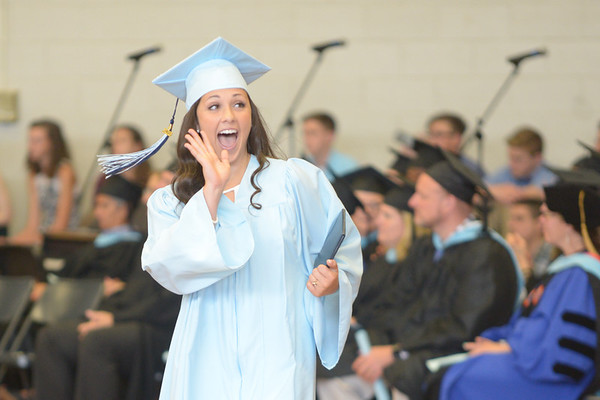 JIM VAIKNORAS/Staff photo Christine Ciccone waves to the crowd after getting her diploma at Triton's Commencement Saturday in the school's field house.