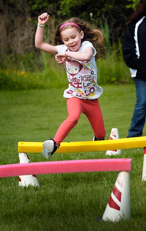 BRYAN EATON/Staff Photo. Lindsay Longacre, 6, runs through at hurdle relay at Amesbury Elementary School on Thursday. She was participating the Annual Field Days competition, one of the schoo's yearend activities.