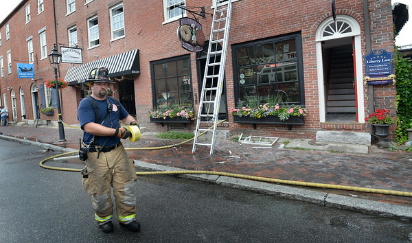 BRYAN EATON/Staff photo. A Newburyport firefighter tapes off the front of Abraham's Bagel on Liberty Street in Newburyport after the shop was gutted in a fire that started around 4:15 a.m. Tuesday morning.