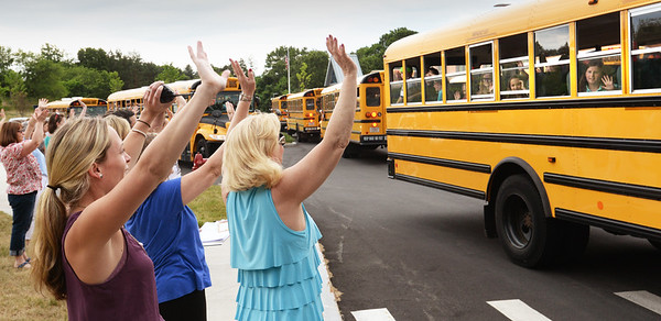 BRYAN EATON/Staff photo. Teachers and staff wave to students at the Bresnahan School in Newburyport yesterday as they break for the summer. Triton District Schools also held their last day of classes.