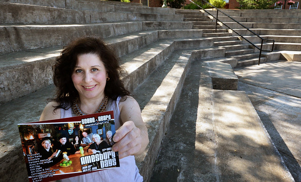 BRYAN EATON/Staff Photo. Michelle DiMascio shows the brochure for this year's Amesbury Days at the Amphitheater in the Upper Millyard where many of the musical events will take place.
