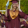 BRYAN EATON/Staff Photo. Serafina Rogers gestures to family members in the audience after receiving her diploma.