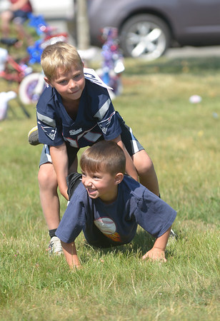 JIM VAIKNORAS/Staff photo Josh Montero , 6, and his brother Chance , 4, compete in the wheelbarrow race Rowley 4th of July festival at Rowley Common Saturday morning.