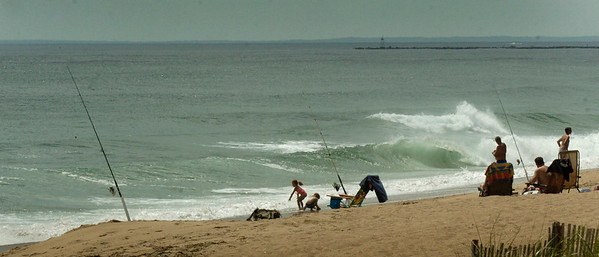 BRYAN EATON/Staff Photo. Monday's nice weather brought fisherman and youngsters alike in the surf at Salisbury Beach, just south of the center.