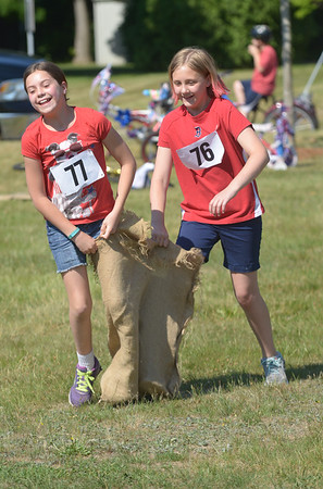 JIM VAIKNORAS/Satff photo Lilly Scire, 11, and Liy Lotarski, 10 compete in the 3 legged sack race  at the Rowley 4th of July festival at Rowley Common Saturday morning.