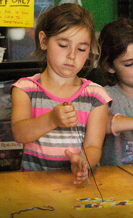 BRYAN EATON/Staff photo. Leah Enes, 7, stretches string to weave a friendship bracelet. She was in the art room of the Newburyport Rec Center for the Department of Youth Services summer program.