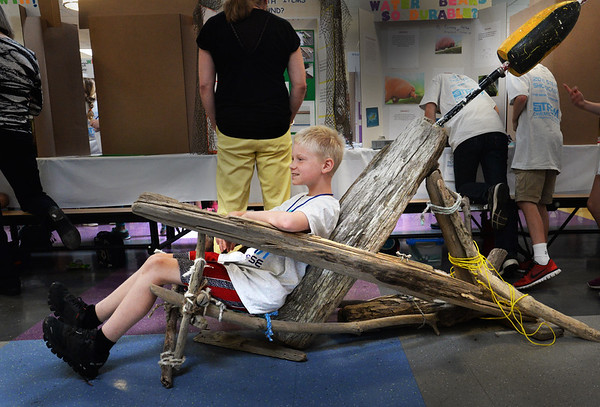 """BRYAN EATON/Staff Photo. Jonas Kenney, 11, sits in his Adrirondack-style chair during the STEM (Science, Technology, Engineering and Math) Showcase at the Upper Molin Elementary School. His problem to solve was """"How Do You Sit at the Beach With Items Found There?"""" The pieces of wood, rope and even a lobster buoy was all found on Plum Island beaches and took him two weeks to create."""