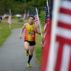 JIM VAIKNORAS/Staff photo Pat Fullerton runs past rows of flags on his way to victory in the 5th Annual Flag Day 5k at Cashman Park.