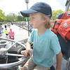 JIM VAIKNORAS/Staff photo Jacob Hill , 6, of Andover takes the wheel of a Coast Guard boat Touch a Boat event along Newburyport's waterfront Saturday. Along with the Coast Guard kids got to get up close to a 28 ft whale boat from Lowell's Boat Shop , the Lynx, Erica Lee II, and many others.