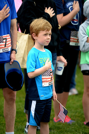 JIM VAIKNORAS/Staff photo Jack Ames, 6, of Newburyport covers his heart during the singing of the National Anthem before the start of the Derek Hines Flag Day 5k at Cashman Park in Newburyport.