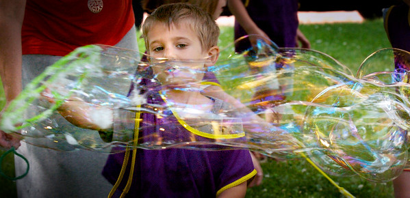 BRYAN EATON/Staff Photo. Sam Naylor, 5, pulls a long bubble across the lawn at Brown Square in Newburyport on Tuesday morning. He was at Bubble Day at the Newburyport Montessori School, one of the year end events at the Inn Street school.