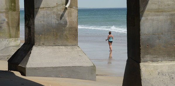 JIM VAIKNORAS/Staff photo A woman jogs along Salisbury Beach  past pillers supporting Blue Ocean on a breezy Sunday morning.