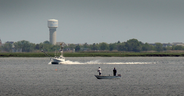 BRYAN EATON/Staff Photo. A fishing boat speeds past two fisherman in the Merrimack River in a view from Joppa Park in Newburyport Tuesday. The week should be good on the water with only a slight chance of rain on Friday and again on the later side of Sunday.