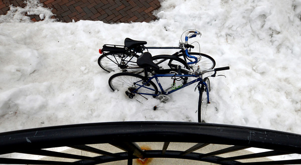 Newburyport: A pair of bikes on Inn Street slowly begin to escape the frozen bonds of winter as the packs of snow begins to melt. Jim Vaiknoras/staff photo